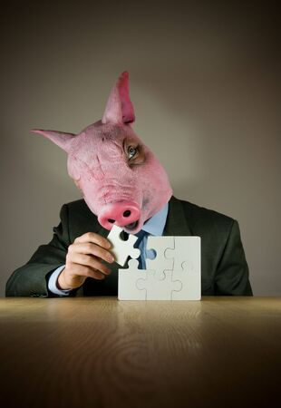 A businessman with a (pigs) mask finishing a puzzle. photo