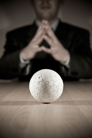 A businesman pondering with focus on a puzzle globe.