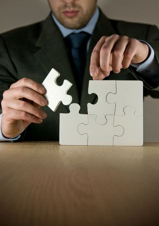 A businessman making a puzzle. Stock Photo - 5863842