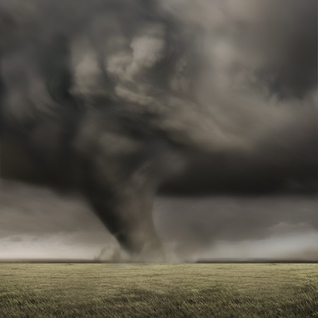 across: A large tornado working its way across fields.
