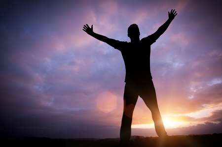 life success: Open Dreams - A man standing with open arms set against a beautiful sunrise. Stock Photo