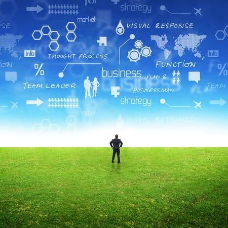 strategy: Un hombre de negocios en un campo con ideas en el cielo. Conceptual