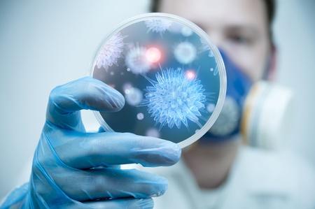 Een wetenschapper die een petrischaal met Virus en bacterie cellen.