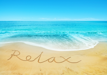 sand writing: Relaxing Beach - Relax written in the sand  Stock Photo
