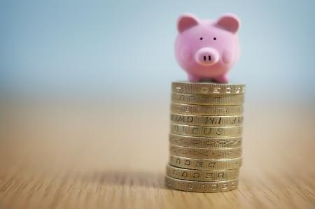 piggy bank: Small Beginnings - Micro Piggy Bank on top of coins  Money concept