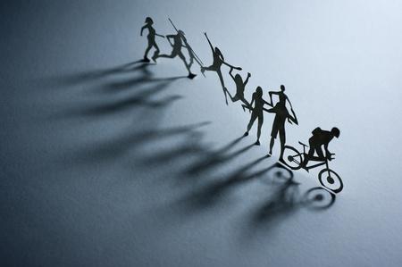 Niños ayudando: Una fila de gente de papel - Fotografía macro Foto de archivo