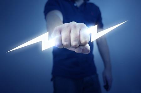 pu�os cerrados: Un hombre que sostiene un rayo el�ctrico estilizado.