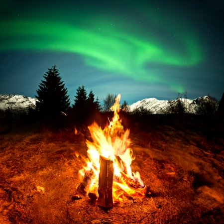 adventure holiday: Watching the Northern lights sat by a warm camp fire  Stock Photo
