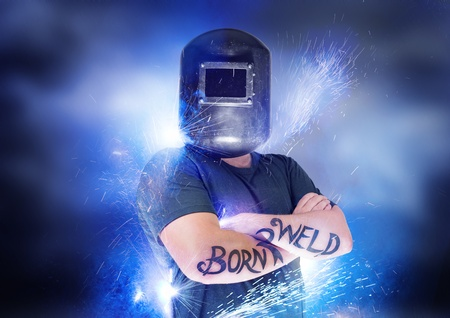 Born To Weld. Dramatic shot of a welder with blue sparks. photo