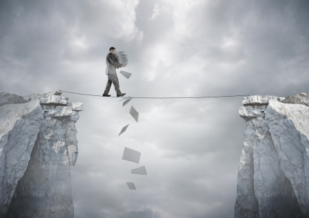 stability: Business Balance - A businessman carrying paperwork walking over a tight rope.
