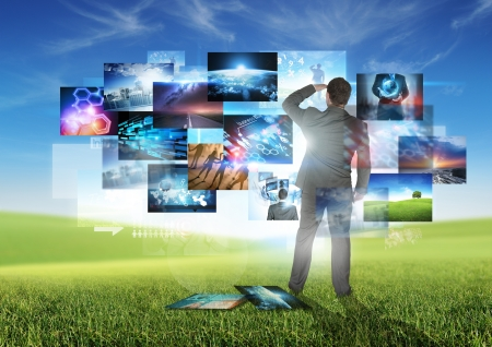 Business Communication - A businessman looking at floating media images. Stock Photo - 21382114