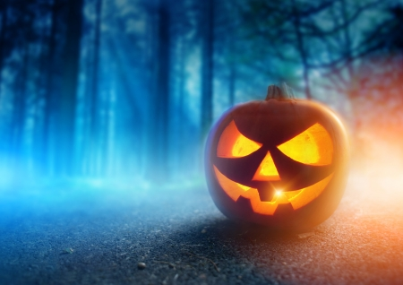 halloween background: A glowing Jack O Lantern in adark mist Forest on Halloween