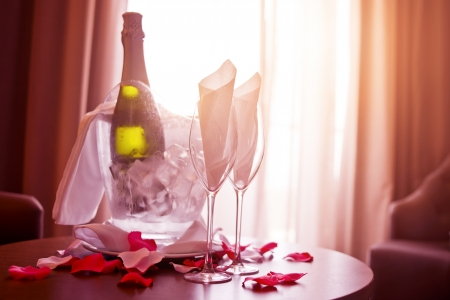 fine dining: A bottle of Champagne and two glasses with romantic rose petals.