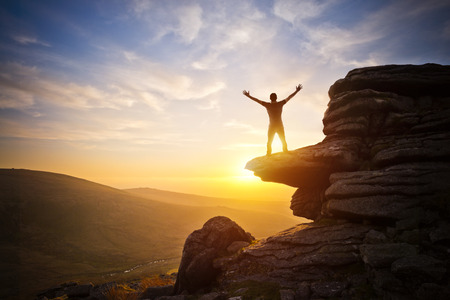 mountain man: A person expressing freedom - reaching up into the sky against a sunset.