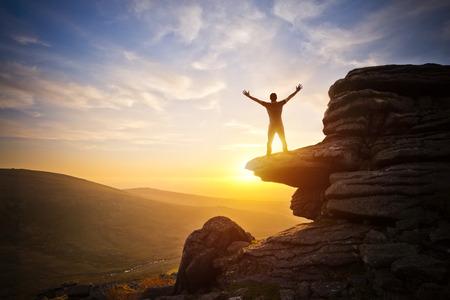 gente saltando: Una persona que expresa la libertad - alcanzando hacia el cielo en contra de una puesta de sol.