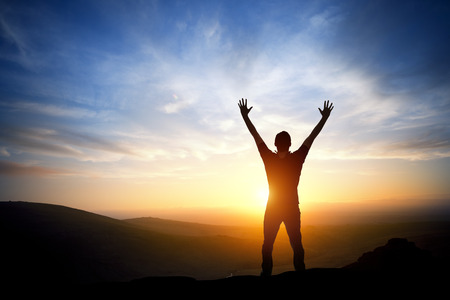 male arm: Fresh New Morning - A person reaching up on a bright morning sunrise. Stock Photo