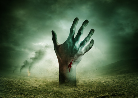 Zombie breakout - Contaminated Land with a zombie hand rising from the ground.. photo