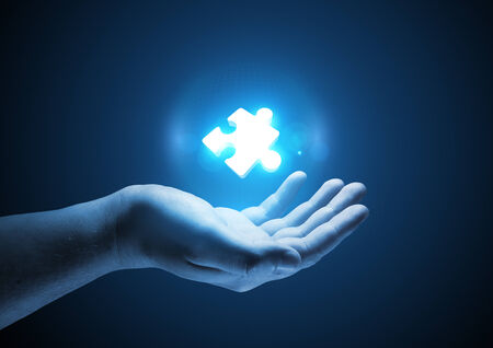 creative answers: Puzzle Solutions. Conceptual illustration. A man holding a glowing single puzzle piece. Stock Photo