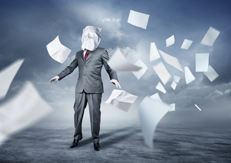 A businessmans face covered in paperwork. Business concept. photo