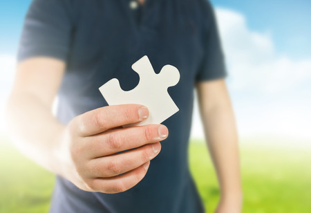 role model: A man holding the missing puzzle piece.