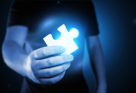 seeking solution: A man holding the missing puzzle piece.