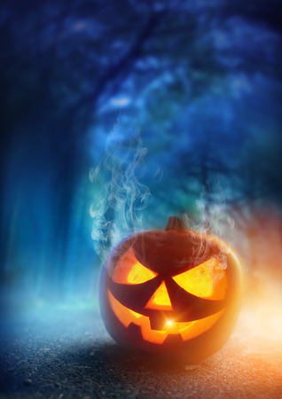 A glowing Jack O Lantern in adark mist Forest on Halloween... photo
