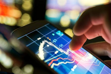 株式市場のデータをチェックする携帯電話を使用して実業家。