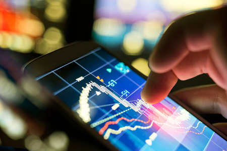 Borsa verileri kontrol için bir cep telefonu kullanan bir işadamı.