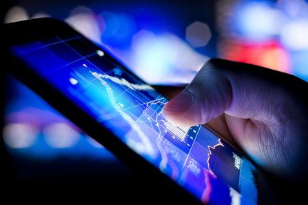 impuestos: Una persona de comprobar los datos del mercado de valores en un dispositivo móvil. Foto de archivo