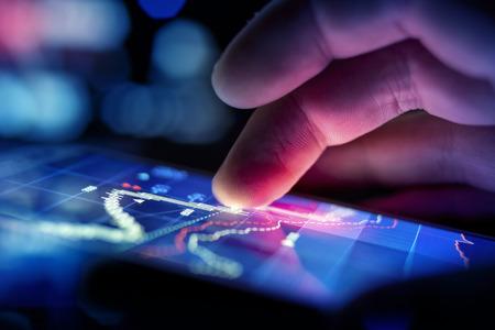 alrededor del mundo: Un hombre de negocios de la ciudad usando un dispositivo m�vil para revisar las acciones y los datos del mercado. Cierre de tiro.