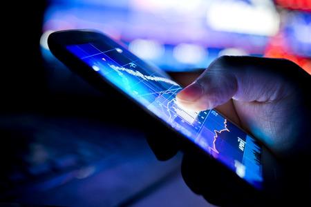 acion: Un hombre de negocios de la ciudad usando un dispositivo móvil para revisar las acciones y los datos del mercado. Cierre de tiro.