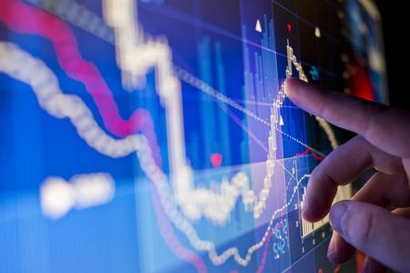 ouvrier: Un travailleur de la ville analyse des données boursières sur un moniteur. Banque d'images