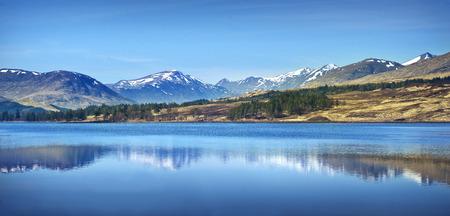 スコットランドのハイランド地方を風景します。スコットランド オナ晴れた日の湖の山の範囲反射。