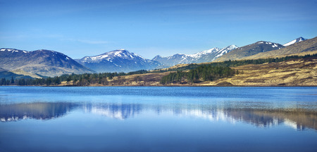 Scottish Highlands Landscape. Mountain range reflections on a lake in Scotland ona  sunny day.