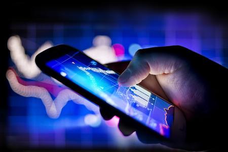 bar charts: Una persona con un teléfono móvil para rastrear las existencias en tiempo real y las acciones de datos
