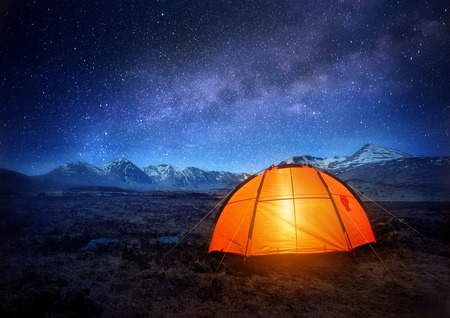 A camping tent glows under a night sky full of stars. Outdoor Camping adventure. Stock Photo