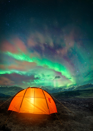 adventure holiday: A camping tent glowing under the Northern Lights. Night time camping scene.