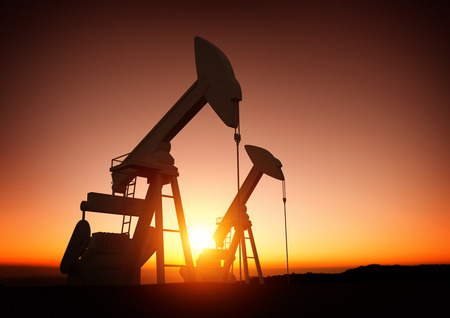 commodities: Oil and Energy Industry. A field of oil pumps against a sunset. Oil prices, energy and economic commodities. Stock Photo