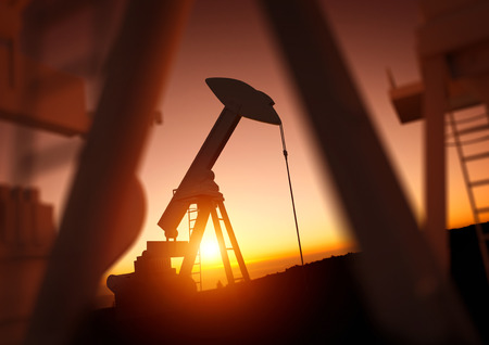 industry: Oil and Energy Industry. A field of oil pumps against a sunset. Oil prices, energy and economic commodities. Stock Photo