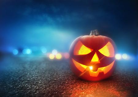 Halloween Night. A Jack O Lantern Pumpkin glowing orange on Halloween evening.