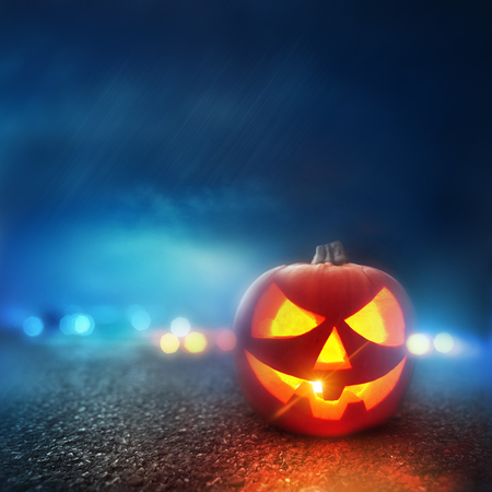party night: Halloween Evening. A Jack O Lantern Pumpkin glowing orange on Halloween evening. Stock Photo