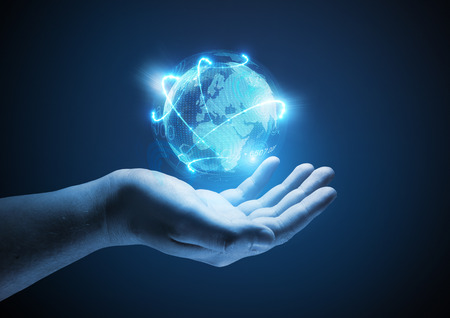 Connected World. Conceptual business  illustration. A man holding a glowing projection of the world. Standard-Bild