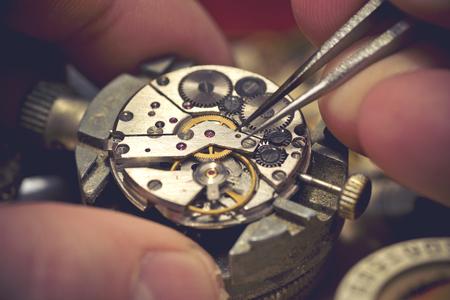 Travailler sur une montre mécanique. A des horlogers travaillent dessus. Les travaux à l'intérieur d'une montre mécanique millésime. Banque d'images - 52013803