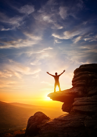 freedom concept: A person reaching up from a high point, set against a sunset. Expressing freedom Stock Photo