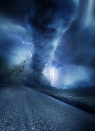 lightning storm: Powerful Tornado with debris on a road. Lightning illuminates the tornado.