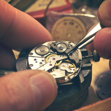 watchmaker: Working On A Mechanical Watch. A watch makers work top. The inside workings of a vintage mechanical watch.