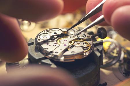 Trabajando en un reloj mecánico. A fabricantes de relojes funcionan superior. El funcionamiento dentro de un reloj mecánico de la vendimia.