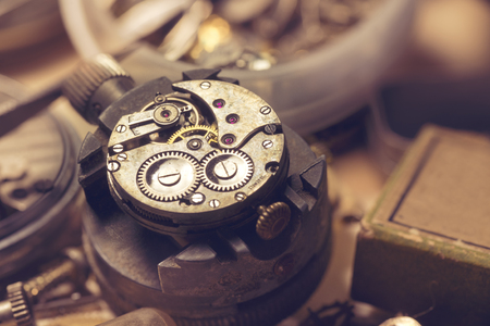 watchmaker: Old Watchmaker Studio. A watch makers work top. The inside workings of a vintage mechanical watch.