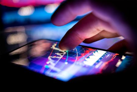 Un empresario comprobar los gráficos de valores en un dispositivo móvil. La tecnología y el trabajo sobre la marcha.