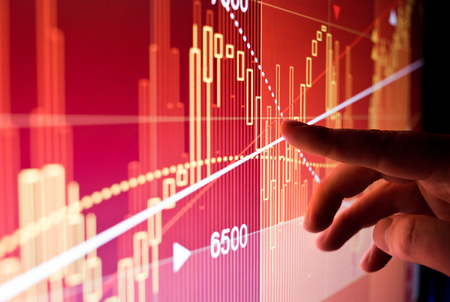 A city worker Analysing illustrated stock market financial  data on a screen. Stock Photo